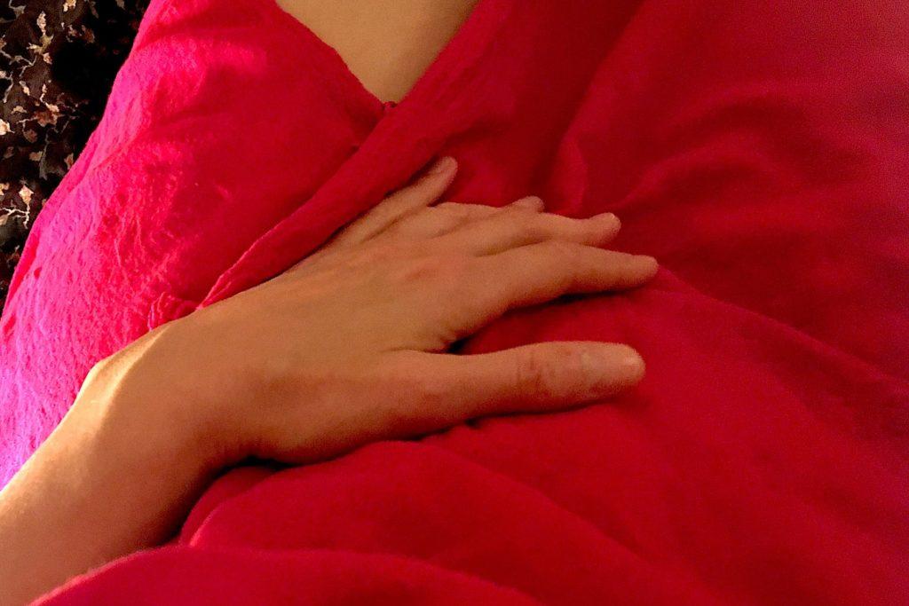 Photo d'une personne en sarong rouge avec la main posée sur les parties intimes.