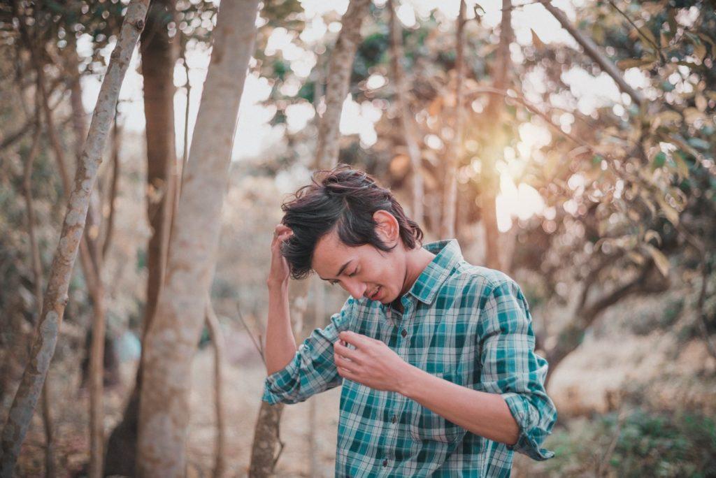 Photo d'une personne dans la forêt avec la tête penchée en avant.