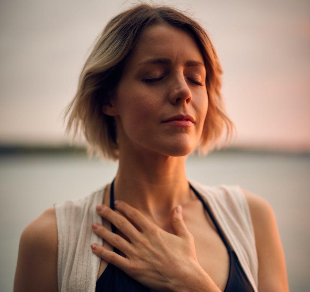 Photo d'une femme avec la main sur le coeur en plan serré sur le visage.