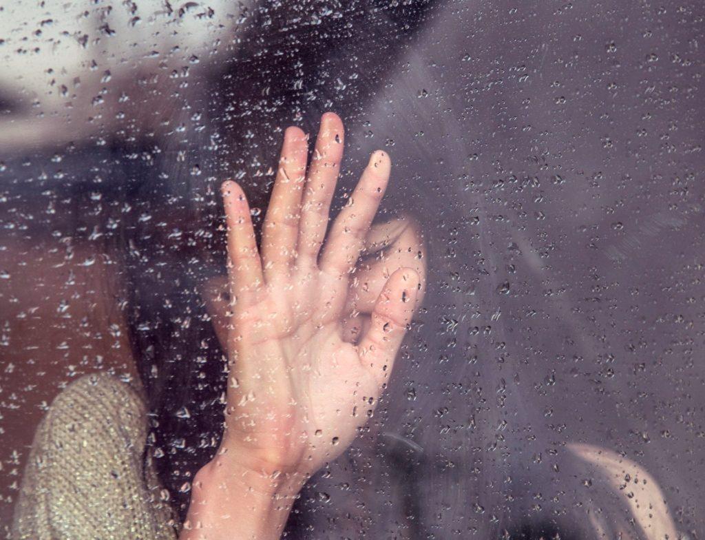 Photo d'une femme avec la main sur une vitre pleine de gouttes de pluie.