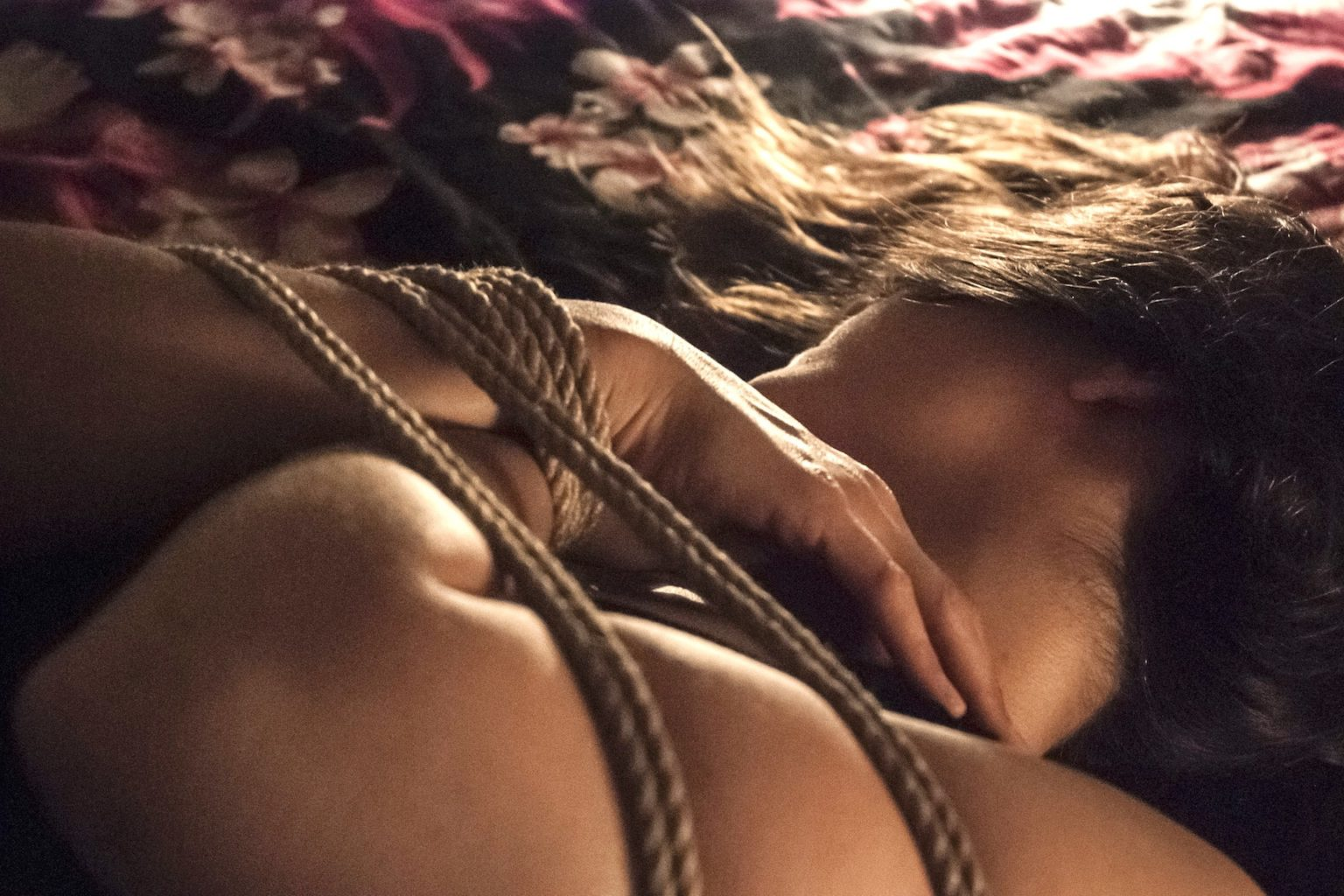Photo d'une personne couchée par terre et attachée avec les bras sur la poitrine.