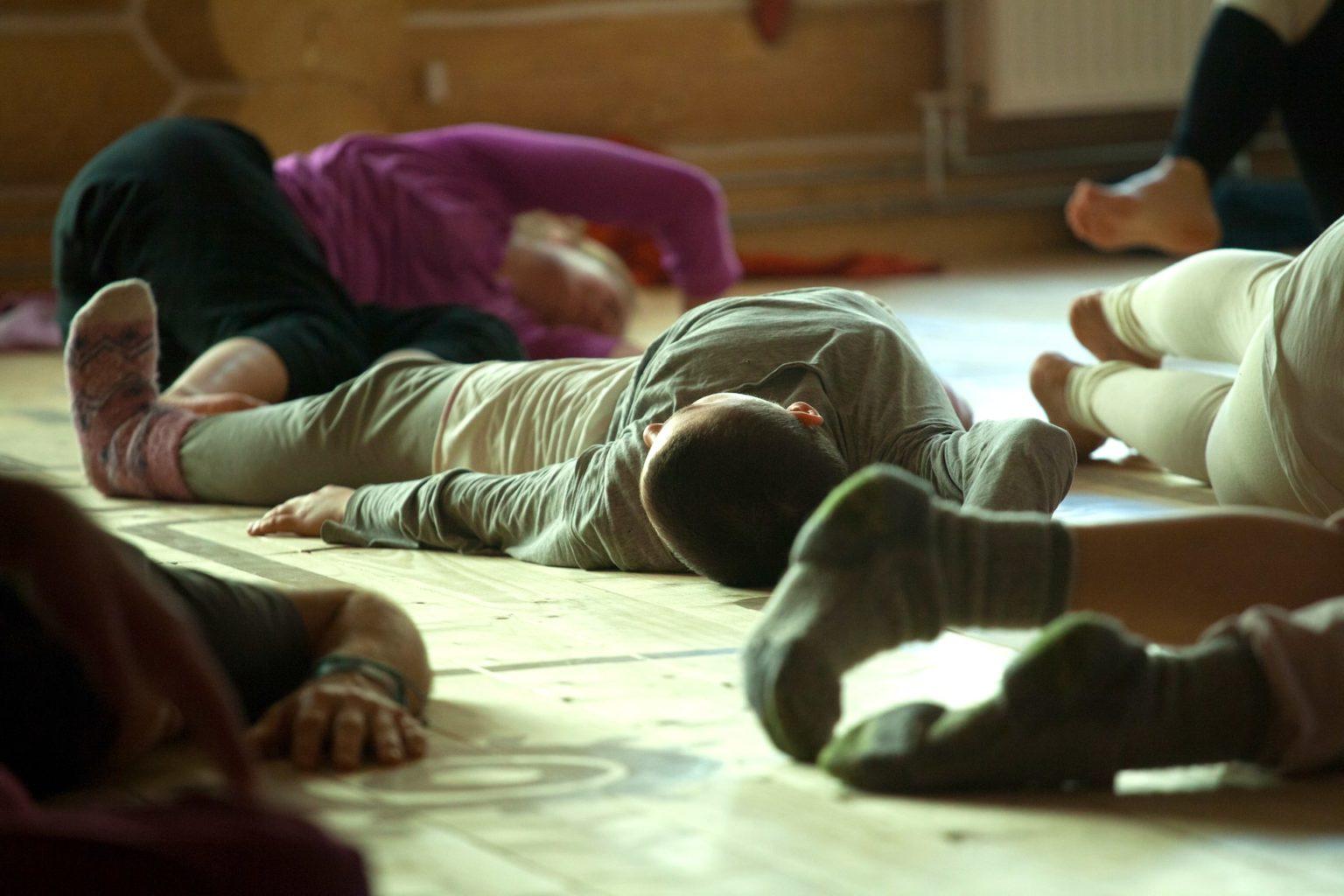 Photo de plusieurs personnes couchées par terre et en mouvement.