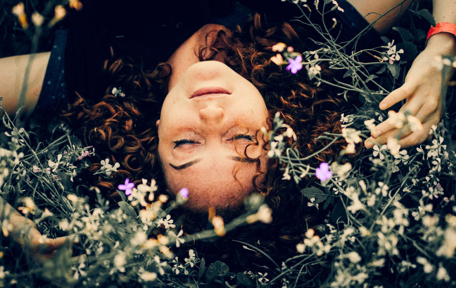 Photo d'une femme couchée dans l'herbe avec des fleurs.